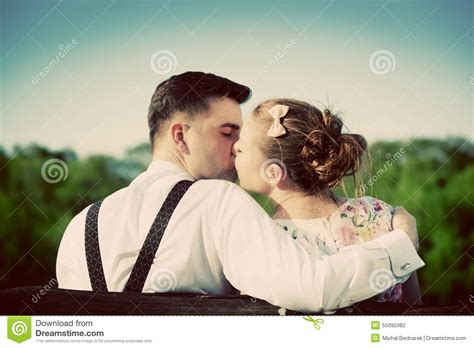 bench couple shirt young couple in love kissing on a bench in park vintage