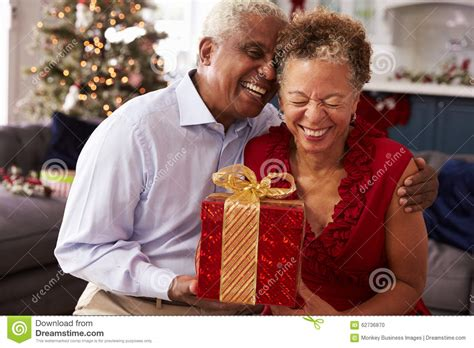 senior couple exchanging christmas gifts at home stock