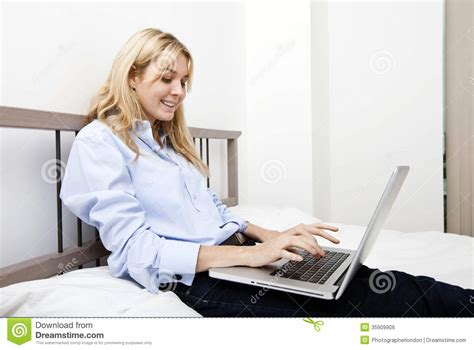 laptop in bed smiling businesswoman using laptop in bed royalty free