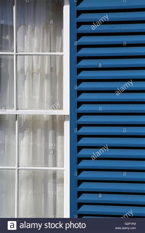 White Curtains With Blue Trim Decorating Blue Window Shutters And A White Curtain Decorate A Window In Battery Stock Photo Royalty Free