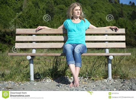 sitting on bench young woman sitting on bench at beach royalty free stock