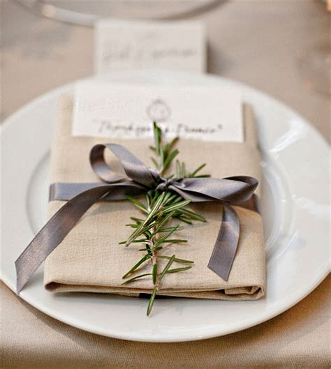 setting table napkin ribbon wrapped around napkin at place setting sprig of