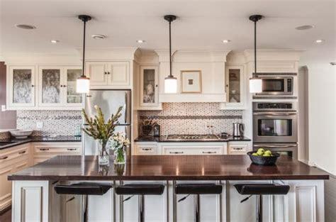 Dazzling pendant lights above a white kitchen island with dark granite