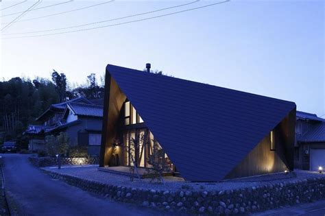 angled roof home surrounded by rock wall and protected by folded roof