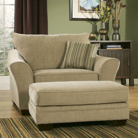 Marvelous Ottoman To Sit On #7: Classic-creamy-oversized-accent-chair-with-stripe-patterned-cushion-and-footrest-on-stripe-patterned-area-rug.jpg