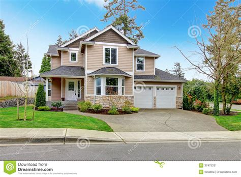 beautiful beige siding house with stoned base stock image