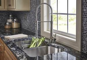 Trends In Kitchen Backsplashes glass penny tile backsplash with a stainless steel faucet