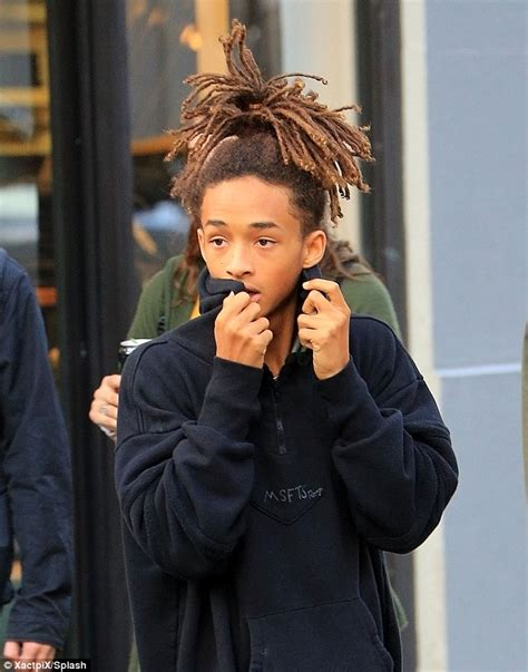jaden smith ties his dreadlocks into a high knot while