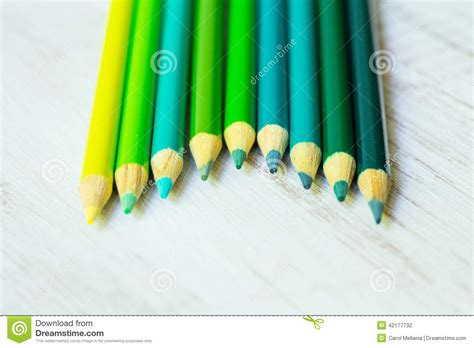 green colored blue and green colored pencils in a row on white stock
