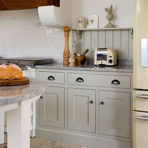 grey shaker style kitchen with white splash back and cup