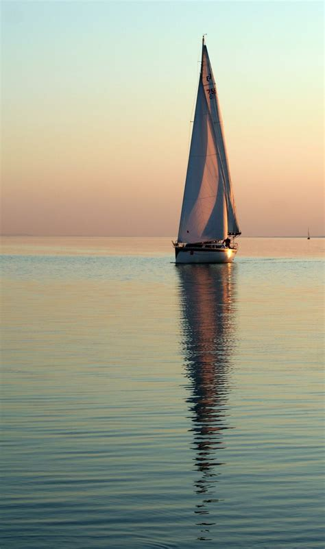 sailboat on water sailing calm waters and clear evening sky sailing