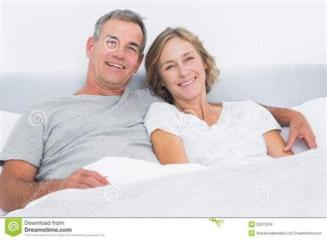cuddle in bed happy couple cuddling in bed looking at camera stock photo image 32515318