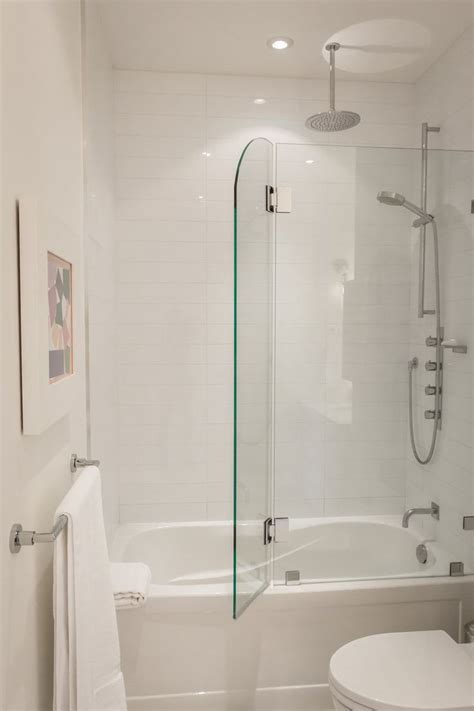 glass doors small bathroom:  white bathroom with glass door that opens for shower in bathtub