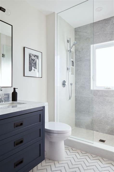 glass shower  navy blue vanity  chevron tile floor