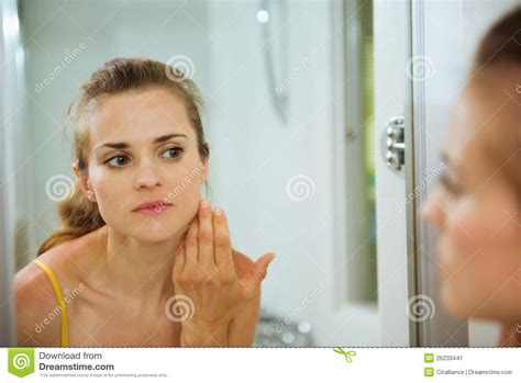 bathroom facial woman checking her face in mirror in bathroom stock image