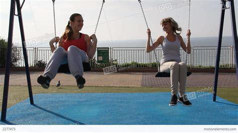 swinging people two girls swinging on a swing stock video footage 2277473
