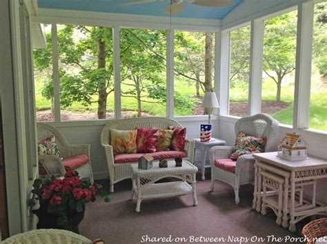 screened in porch with wicker furniture a haint blue ceiling