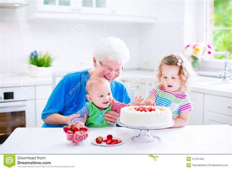 Loving Family Kitchen Furniture grandmother baking cake with kids stock photo image