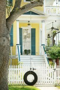yellow house with door white picket fences country houses blue shutters blue