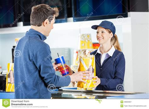 seller giving popcorn and drink to man at stock photo