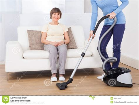 cleaning couches at home caretaker cleaning floor while senior woman sitting on sofa stock photo image 44412622
