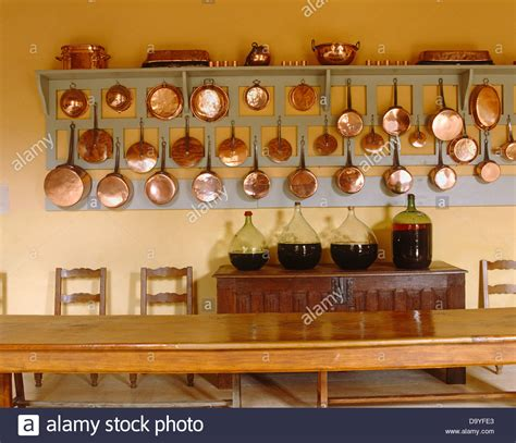 rows of copper pots and pans on wooden wall rack above