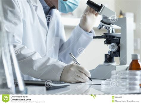 conducting research scientist conducting research with microscope stock photo