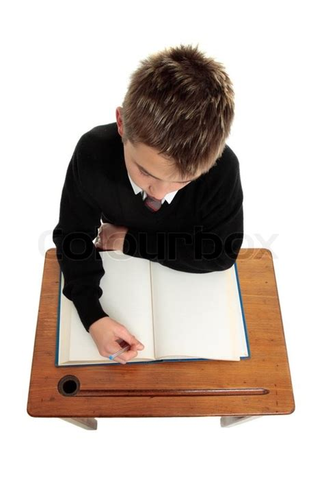student sitting at desk conscientious school boy student sitting at a desk with an