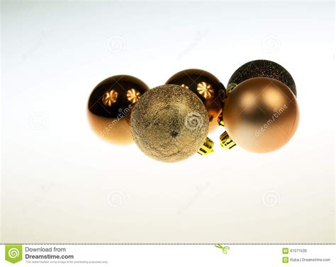 five golden and brown christmas baubles together on white