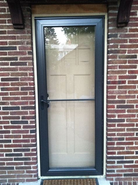 Decorating Wonderful White Andersen Storm Doors With Green Shingle Siding And Wooden Flooring Andersen Door Handle Template