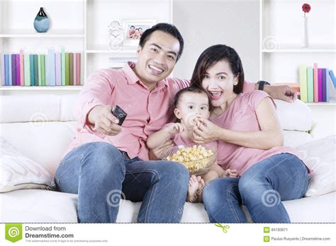 family watching tv with popcorn in living room stock photo chinese family watching tv on sofa together stock image