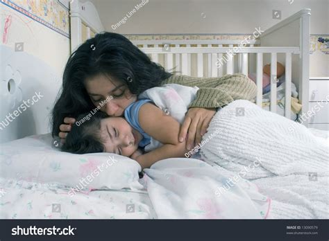 how to get her in bed mother saying goodnight tucking her daughter stock photo