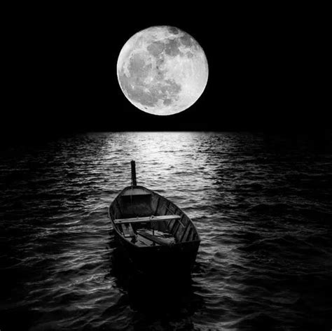 row boat lights at night black and white moonlight on the water with reflection and
