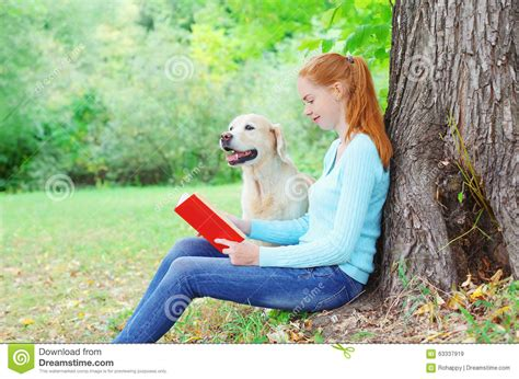 golden retriever books happy and owner in summer park royalty free stock