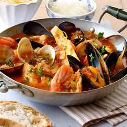 cucinare brodo di pesce zuppa di pesce ricetta con pomodori e misto pesce