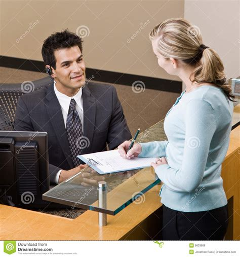 What Is Front Desk Receptionist by Receptionist Greeting At Front Desk Stock Photo