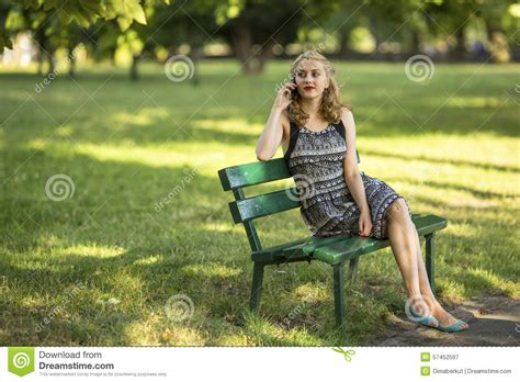 bench women young woman sitting on a park bench talking on a cell
