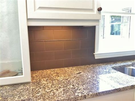 4x8 porcelain tile with bronze accent at kitchen