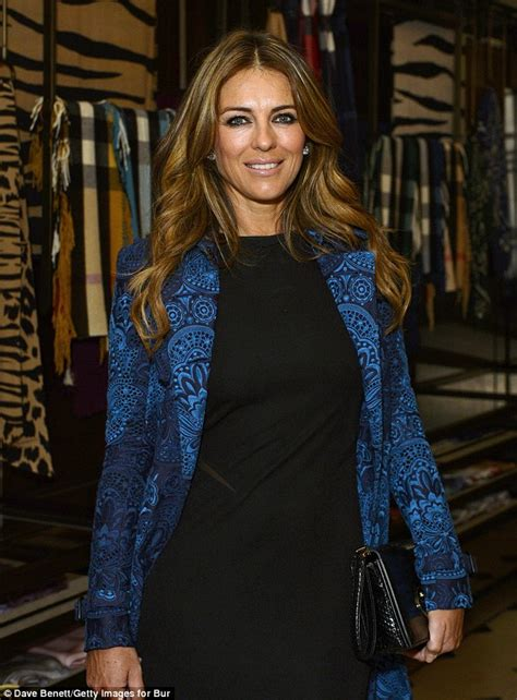 Liz Hurley In Brittish In Style by Elizabeth Hurley In A Black Minidress And Royal Blue Coat