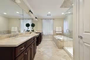 luxury master bathroom floor swirled beige tile fills the lower half of this expansive bathroom