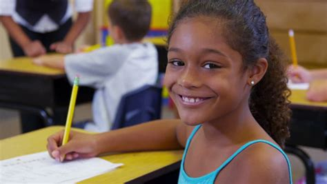 Smile Kls 3 Sd Student Book boy sitting at school desk looks up and smiles at