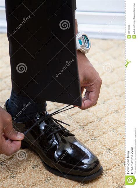 tying shoe laces on black dress shoes stock