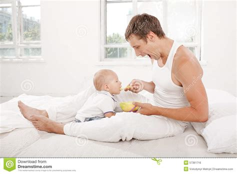 in daddys bed young father with his nine months old son on the bed at