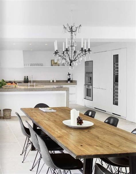 mixing modern chandelier with a traditional the rustic dining table paired with modern eames chairs