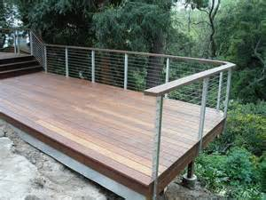 cable railing shown with stainless side mounted posts and wooden top rail