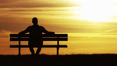person sitting on a bench 4k silhouette of a man sitting on a bench admiring the