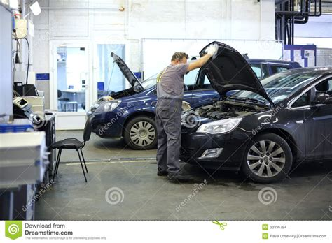 small cars black mechanic in overalls opened hood of black car stock photo