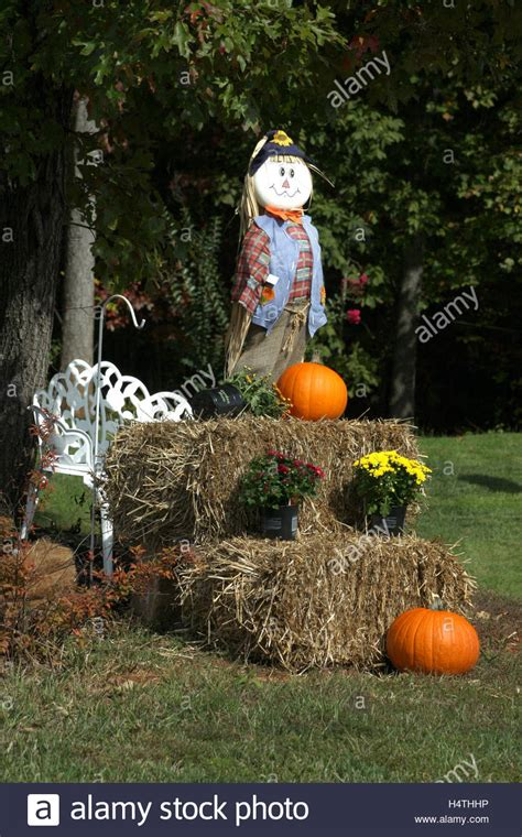 outdoor fall decoration with scarecrow hay mums and