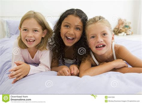three in a bed three young girls lying on a bed in their pajamas stock photo image 6441250