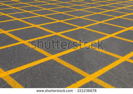 pattern of yellow lines on the roadway diagonal yellow lines forming grid asphalt stock photo